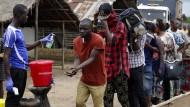 Männer, die ein Gebiet unter Ebola-Quarantäne in Sierra Leone verlassen, werden auf erhöhte Temperatur untersucht.
