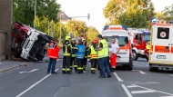 Feuerwehrleute und Rettungssanitäter stehen am Montag auf einer Straße in Coburg an der Unfallstelle.