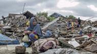Eine Überlebende des Tsunamis sitzt auf einem Haufen Schutt.