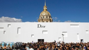 People wait outside a temporary venue near the Invalides dome before the Spring/Summer 2013 women's ready-to-wear fashion show for French house Dior during Paris fashion week
