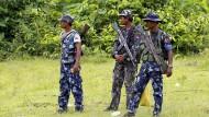 Polizisten stehen im Herbst 2017 in einem Dorf im Westen Myanmars, in dessen Nähe ein Hindu-Massengrab gefunden wurde. Die Arsa-Miliz steht unter Verdacht, die Morde begangen zu haben.