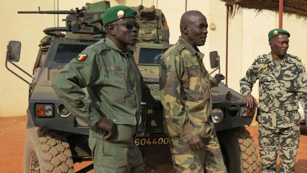 Malian military soldiers stand near an armoured vehicle that belongs to the French Army at the Malian military Command Post in Sevare