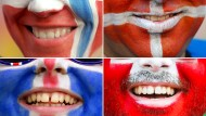 Fußballfans mit geschminkten Gesichtern aus Norwegen, Dänemark, Island und der Schweiz (von oben links nach unten rechts) . Im Weltglücksbericht nehmen Norwegen, Dänemark, Island, die Schweiz und Finnland die ersten Plätze ein.