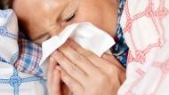 Eine Frau putzt sich die Nase (Symbolbild).