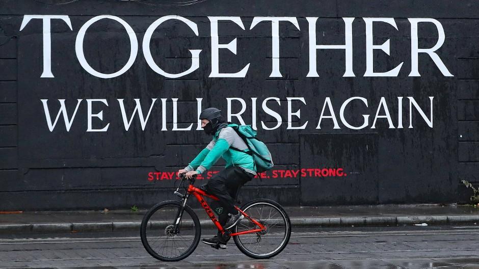 """Ein Fahrradfahrer mit Maske fährt in Dublin an der Aufschrift """"Together we will rise again"""" (""""Zusammen werden wir wieder aufstehen"""") vorbei."""