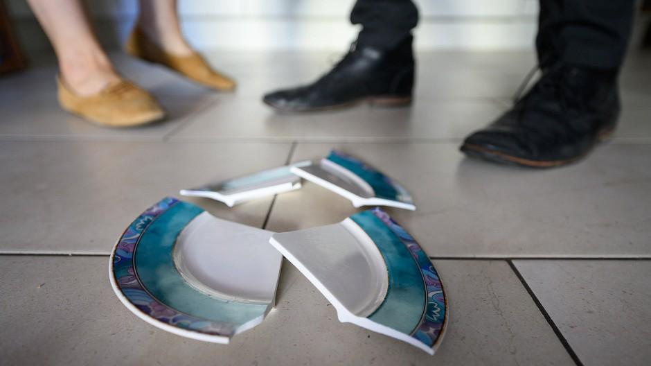 Ein zerbrochener Teller liegt auf dem Boden vor den Füßen eines Paares (Symbolbild).