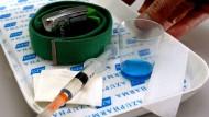 So kann Methadon in Haft verabreicht werden: Ein Tablett mit Heroinspritze, einem Becher für Methadon sowie ein Gurt zum Abbinden des Blutes.