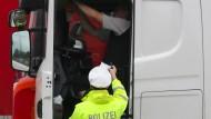 Ein Polizist kontrolliert im August einen Lastwagenfahrer an einem Rastplatz in Nordrhein-Westfalen.