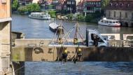 """""""Reverse Graffiti"""": Klaus Dauven und ein Mitstreiter arbeiten an der Unteren Brücke in Bamberg."""