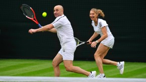 Andre Agassi of the US and Germany's Steffi Graf react during their mixed doubles match against Tim Henman and Kim Clijsters under the newly completed Centre Court roof at Wimbledon in London