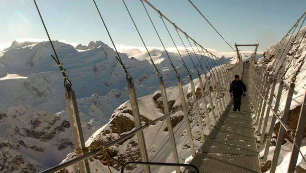 A construction worker walks on the Titlis Cliff Walk suspension bridge at the Mount Titlis skiing area near the Swiss mountain resort of Engelberg