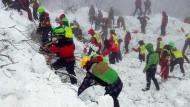 Rettungskräfte arbeiten sich in der Nähe des Hotels Rigopiano auf der Suche nach den Vermissten durch Schneemassen.
