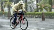 """Bei den vom Himmel stürzenden Wassermassen von Taifun """"Megi"""" sind auch das schützende Cape und die Regenhose dieses fahrradfahrenden Taiwaners komplett durchnässt."""