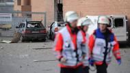 Rettungskräfte gehen an zerstörten Autos im Industriegebiet in Euskirchen vorbei.