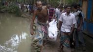 Bewohner eines nahen Dorfes transportieren eines der geborgenen Opfer in einem Tuch ab.