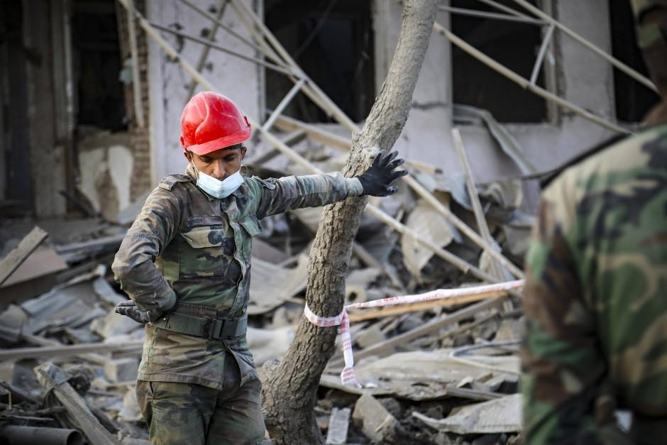 Ein aserbaidschanischer Soldat mit Corona-Maske in der Nähe eines zerstörten Hauses in Gandscha