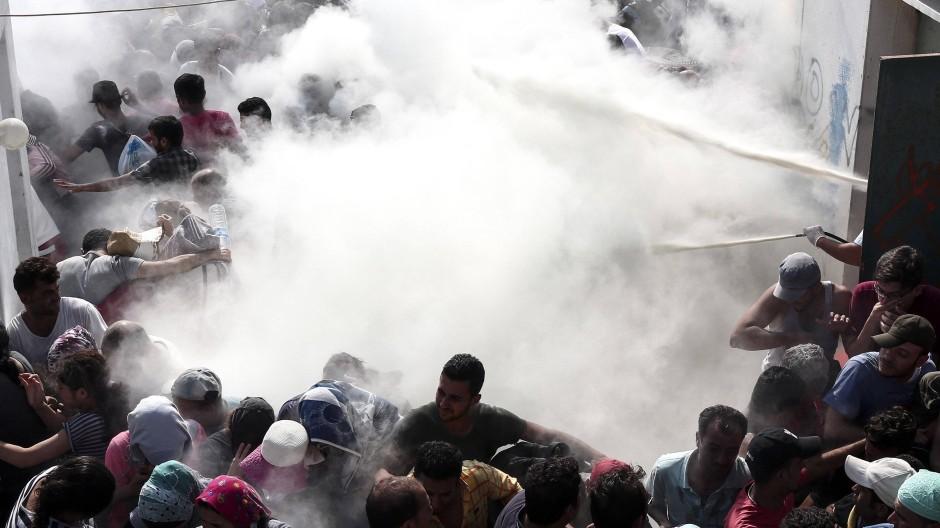 Mit dem Schaum aus Feuerlöschern gehen Polizisten gegen die Menge vor.