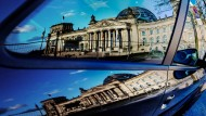 The Berlin Reichstag is reflected in a car window