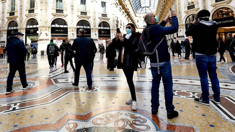 Touristen tragen Mundschutz in der Galleria Vittorio Emanuele II in Mailand und machen Fotos mit ihren Smartphones.