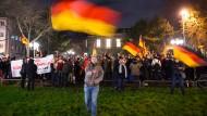 """Ein """"Bogida""""-Demonstrant schwenkt in Bonn die deutsche Flagge."""