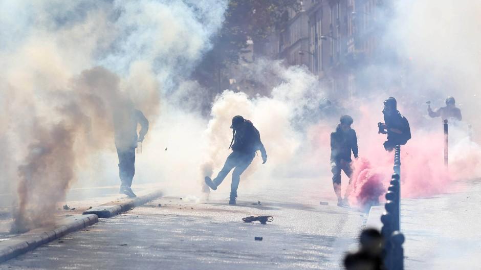 Demonstranten treten gegen Tränengasbehälter am Samstag auf einer Straße in Paris.