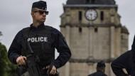 Ein schwer bewaffneter Polizist sichert die Kirche von Saint-Etienne-du-Rouvray, nahe Rouen