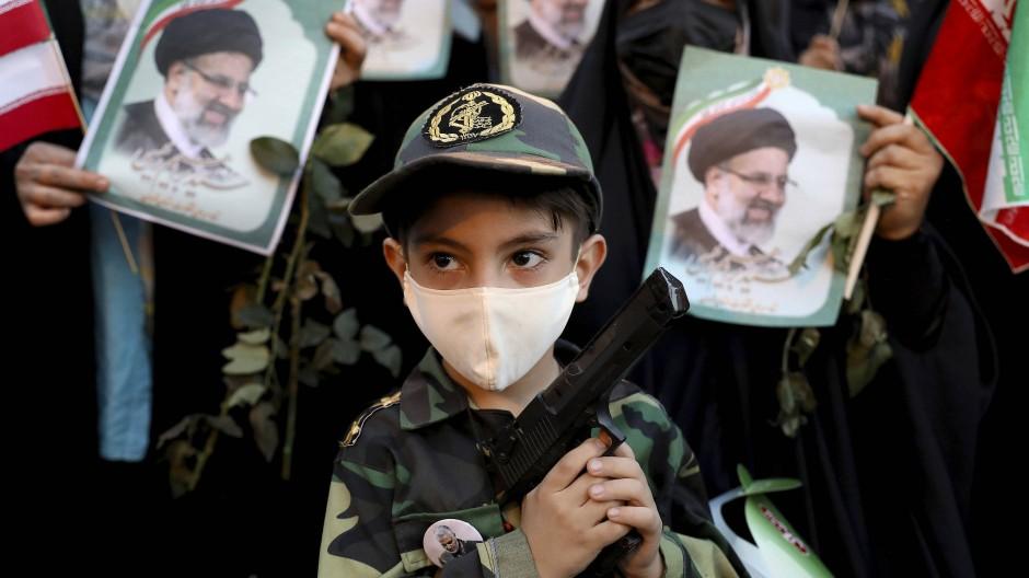 Ein Kind in Uniform der Revolutionswächter bei einer Siegesfeier für Raisi