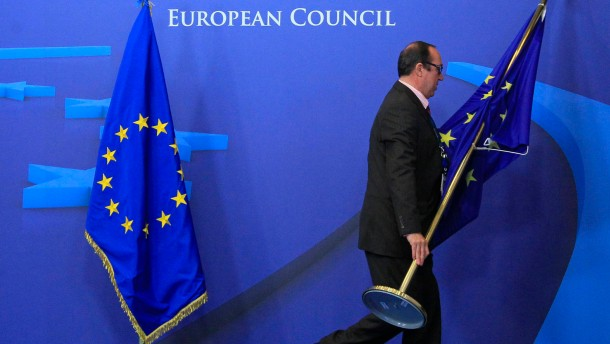 An employee at the EU council adjusts European Union flags at the entrance of the council headquarters for an European Union leaders summit discussing the European Union's long-term budget in Brussels