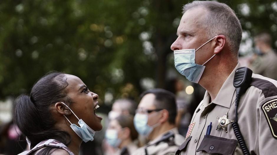 Eine Frau schreit in Minneapolis während einer Demonstration nach dem Tod von George Floyd einen Polizisten an.