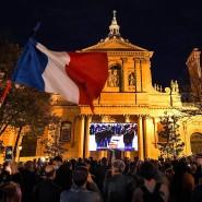 Auf dem Place de la Sorbonne blicken Zuschauer auf eine Übertragung der Trauerzeremonie für Samuel Paty.