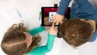 Die Möglichkeit hat nicht jedes Kind: Ein Junge und ein Mädchen arbeiten im März auf der Bildungsmesse Didacta in Stuttgart an einem Tablet