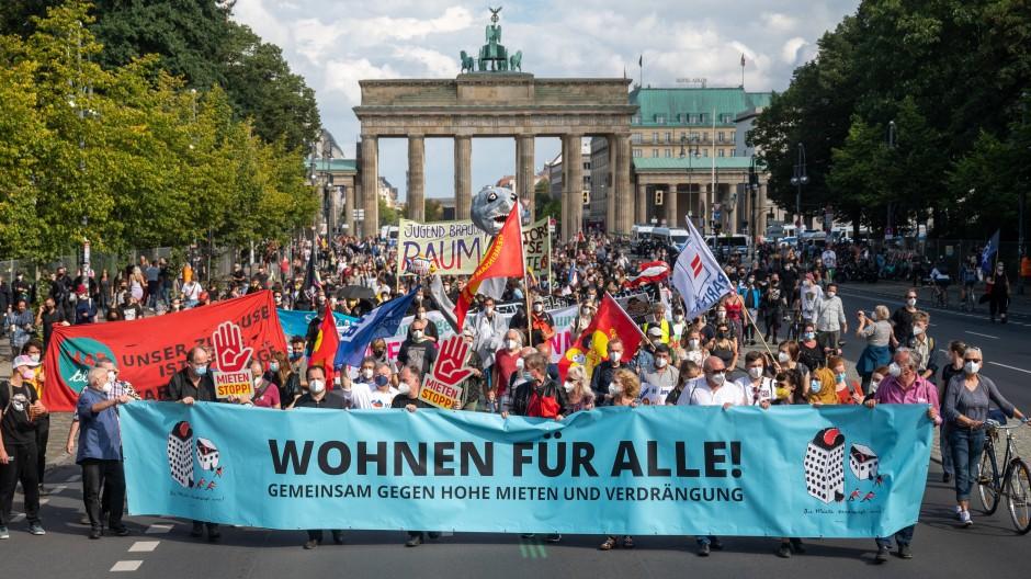 Teilnehmer der Demonstration halten vor dem Brandenburger Tor ein Transparent mit der Aufschrift «Wohnen für Alle!».