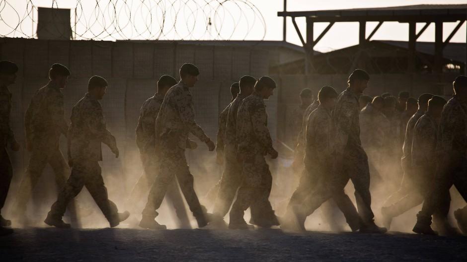 Bundeswehrsoldaten gehen 2013 nach einem Appell über den staubigen Aufmarschplatz des bereits aufgegebenen Stützpunktes in Kundus.