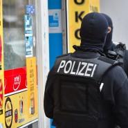 Einsatz gegen organisierte Kriminalität: Vermummte Einsatzkräfte stehen vor einem Kiosk im Stadtteil Neukölln
