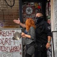 Ein Polizeibeamter führt eine Demonstrantin aus dem abgesperrten Bereich der Weisestraße in Neukölln.