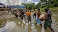 September 2017: Aus Burma geflohene Rohingya transportieren Lebensmittel in ein Flüchtlingscamp.