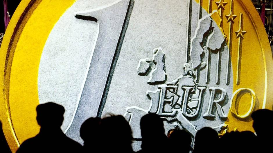 Eine riesige Euro-Münze überragt die Menschen in der Innenstadt von Frankfurt am Main als die ersten Euro-Starterkits mit einem Sortiment von Euro-Münzen ausgegeben werden.