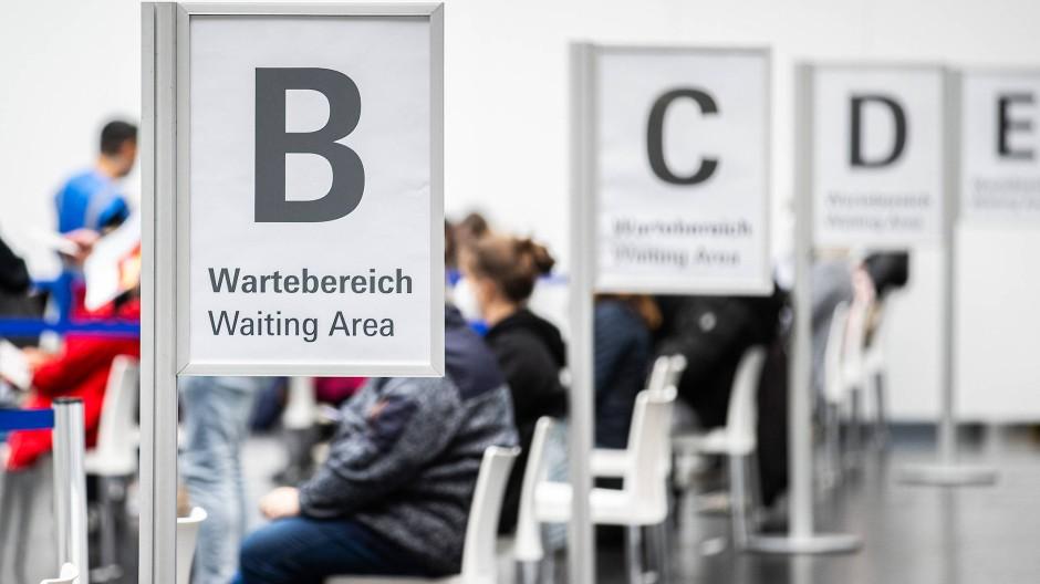 Im Frankfurter Corona Impfzentrum auf dem Messeglände in der Festhalle warten Personen in einem Wartebereich auf ihre Impfung.