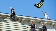 """Polizisten und Aktivisten der """"Identitären Bewegung"""" stehen neben der Quadriga auf dem Brandenburger Tor."""