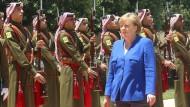 Der Asylstreit lässt sie nicht los. Bundeskanzlerin Merkel schreitet eine Ehrenformation vor dem königlichen Palast in Jordaniens Hauptstadt Amman ab.
