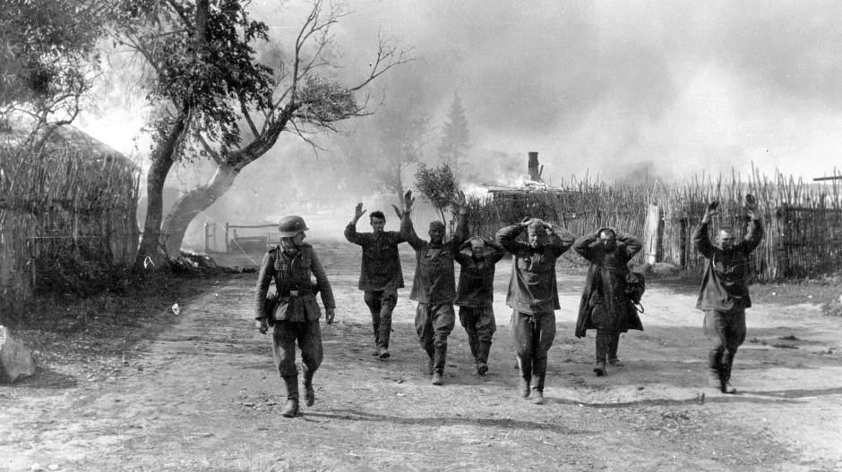 Sowjetische Soldaten werden mit erhobenen Händen in die Gefangenschaft geführt, links ein deutscher Soldat. Von Deutschen aufgenommenes Bild von 1941