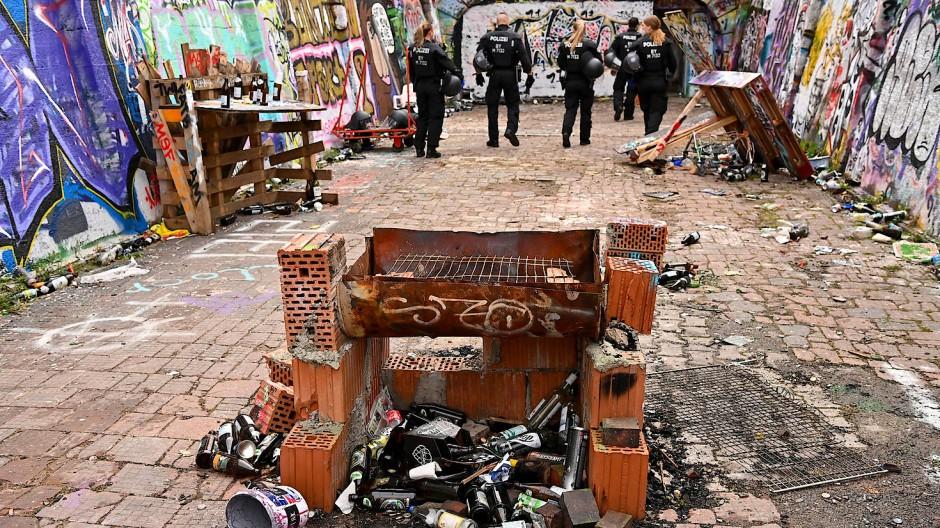 Polizeibeamte stehen am frühen Sonntagmorgen in München auf einem mit unzähligen Flaschen und Spraydosen übersäten Bereich am Schlachthof. Dort wurde zuvor eine illegale Rave-Party aufgelöst.
