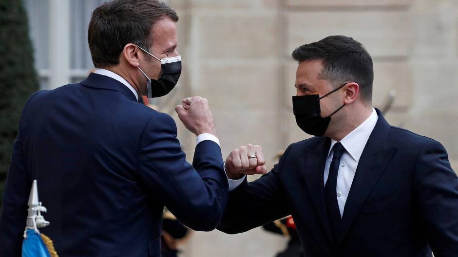 Emmanuel Macron und Wolodymyr Selenskyj begrüßen sich am 16. April vor dem Elysee-Palast mit den Ellbogen