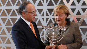 German Chancellor Merkel receives a menorah from President of the Central Council of Jews in Germany Graumann, ahead of a council meeting in Frankfurt