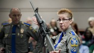2013: Eine Polizistin zeigt bei einer Anhörung in Connecticut ein Bushmaster AR-15. Dasselbe Modell benutzte der Attentäter in the Sandy-Hook-Grundschule.