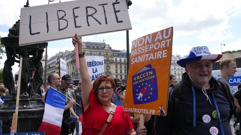 Demonstranten ohne Mund-Nasen-Schutz nehmen am Samstag in Paris an einer Protestaktion gegen Coronamaßnahmen und den Covid-Pass teil.