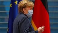 Ungetrennt und unvermischt: Bundeskanzlerin Merkel am 16. Dezember 2020 von Flaggen der Bundesrepublik und der EU