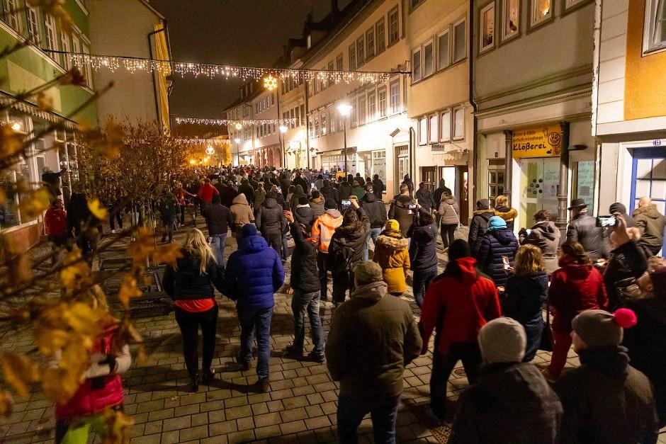 Menschen laufen am Mittwochabend durch die Innenstadt von Hildburghausenund protestieren gegen die neuen Infektionsschutzregeln im Kreis.