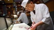 Mitsumori Sakamoto, Küchenchef des Sushi-Restaurants Sushimoto schneidet hinter der Sushi-Theke täglich frischen Fisch zu.