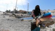 Eine Frau trägt Habseligkeiten durch die ostsyrische Stadt asch-Schaddadi.